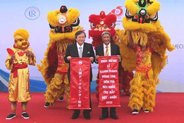 ベトナムの伝統芸能の獅子舞と一緒に記念撮影する高木邦格理事長とグエン・チュオン・ソン病院長